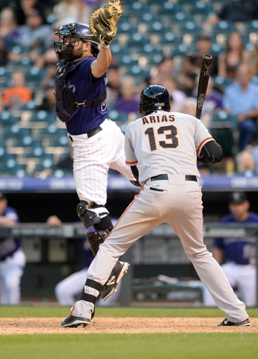 Sep 1, 2014; Denver, CO, USA; Colorado Rockies catcher Michael McKenry (8) jumps up to save a wild pitch over the head of San Francisco Giants third baseman Joaquin Arias (13) in the ninth inning at Coors Field. Mandatory Credit: Ron Chenoy-USA TODAY Sports