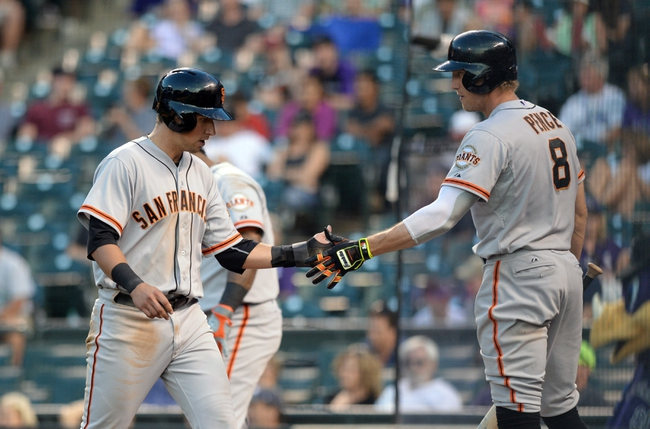 Sep 1, 2014; Denver, CO, USA; San Francisco Giants second baseman Joe Panik (12) is congratulated after scoring by right fielder Hunter Pence (8) in the ninth inning against the Colorado Rockies at Coors Field. Mandatory Credit: Ron Chenoy-USA TODAY Sports