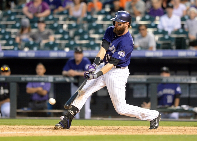 Sep 1, 2014; Denver, CO, USA; Colorado Rockies right fielder Charlie Blackmon (19) hits a walk off RBI single to win the game in the ninth inning against the San Francisco Giants at Coors Field. The Rockies defeated the Giants 10-9. Mandatory Credit: Ron Chenoy-USA TODAY Sports