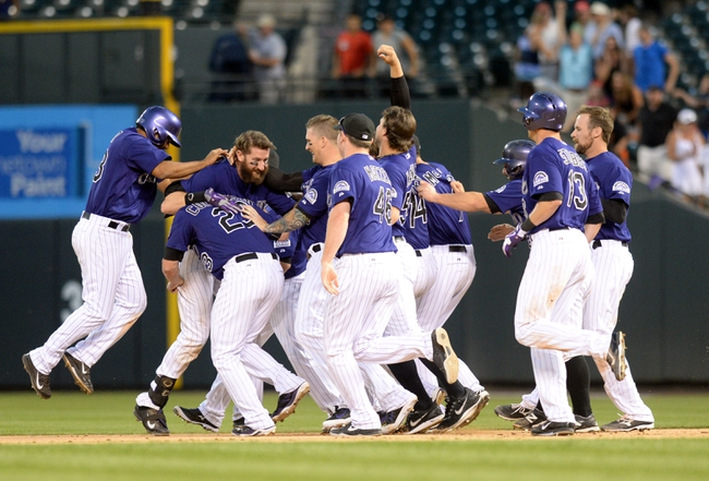Sep 1, 2014; Denver, CO, USA; Colorado Rockies right fielder Charlie Blackmon (19) is congratulated for his walk off RBI single to win the game in the ninth inning against the San Francisco Giants at Coors Field. The Rockies defeated the Giants 10-9. Mandatory Credit: Ron Chenoy-USA TODAY Sports