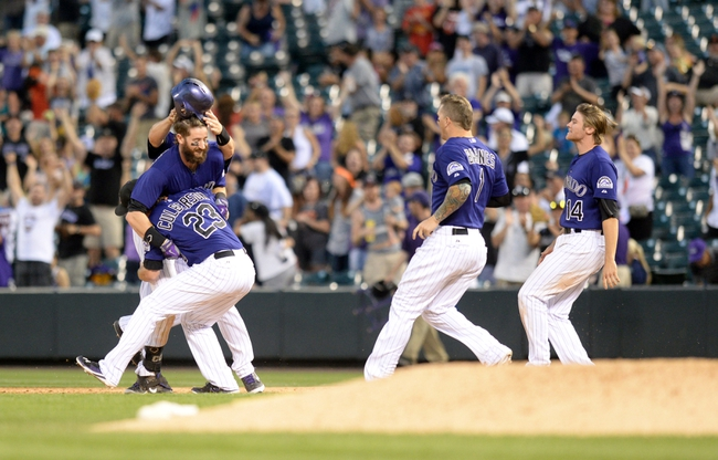 Sep 1, 2014; Denver, CO, USA; Colorado Rockies right fielder Charlie Blackmon (left) is congratulated for his walk off RBI single to win the game in the ninth inning against the San Francisco Giants at Coors Field. The Rockies defeated the Giants 10-9. Mandatory Credit: Ron Chenoy-USA TODAY Sports