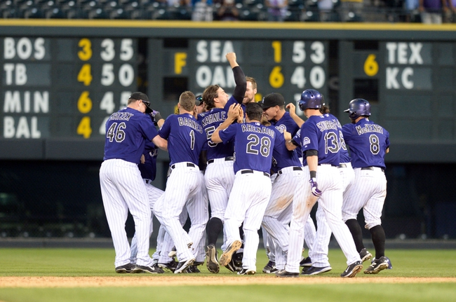 Sep 1, 2014; Denver, CO, USA; Members of the Colorado Rockies react to a walk off RBI single by right fielder Charlie Blackmon (19) (center) in the ninth inning against the San Francisco Giants at Coors Field. The Rockies defeated the Giants 10-9. Mandatory Credit: Ron Chenoy-USA TODAY Sports