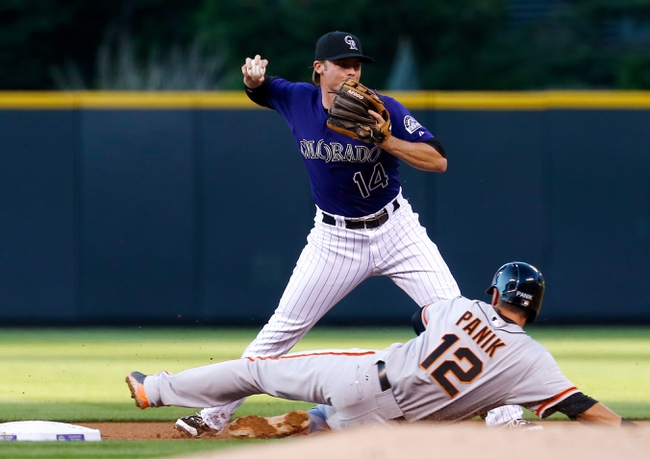 Sep 2, 2014; Denver, CO, USA; Colorado Rockies short stop Josh Rutledge (14) turns a double play against San Francisco Giants second baseman Joe Panik (12) in the first inning at Coors Field. Mandatory Credit: Isaiah J. Downing-USA TODAY Sports