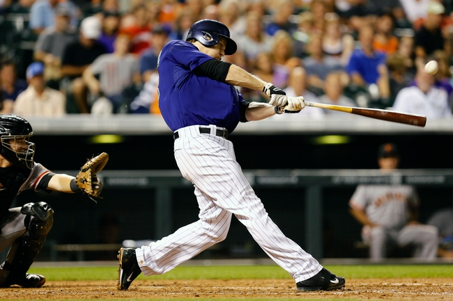 Sep 2, 2014; Denver, CO, USA; Colorado Rockies first baseman Justin Morneau (33) hits a single in the fifth inning against the San Francisco Giants at Coors Field. Mandatory Credit: Isaiah J. Downing-USA TODAY Sports