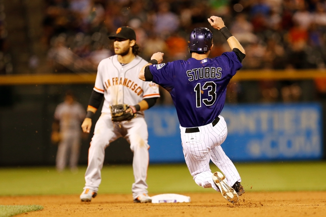 Sep 2, 2014; Denver, CO, USA; Colorado Rockies center fielder Drew Stubbs (13) steals second base against San Francisco Giants short stop Brandon Crawford (35) in the fifth inning at Coors Field. Mandatory Credit: Isaiah J. Downing-USA TODAY Sports