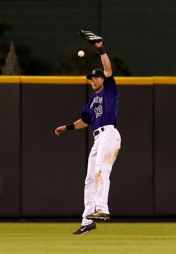 Sep 2, 2014; Denver, CO, USA; Colorado Rockies center fielder Drew Stubbs (13) makes a fielding error against the San Francisco Giants allowing a run to score in the eight inning at Coors Field. Mandatory Credit: Isaiah J. Downing-USA TODAY Sports