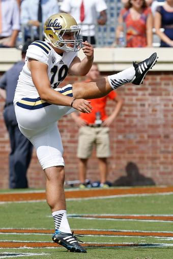 Aug 30, 2014; Charlottesville, VA, USA; UCLA Bruins punter Matt Mengel (19) punts the ball against the Virginia Cavaliers at Scott Stadium. Mandatory Credit: Geoff Burke-USA TODAY Sports