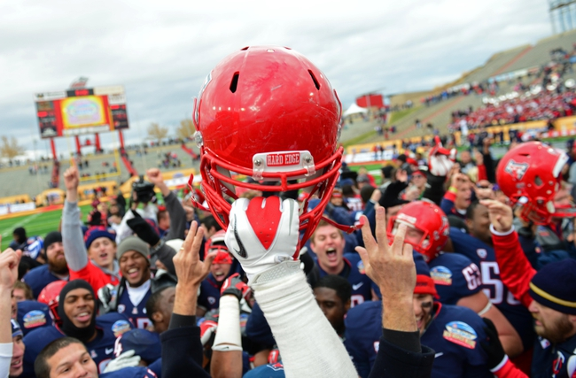 Dec. 15, 2012; Albuquerque, NM, USA; Detailed view of an Arizona Wildcats helmet held in the air by a player as the team celebrates their victory against the Nevada Wolf Pack in the 2012 New Mexico Bowl at University Stadium. Arizona defeated Nevada 49-48. Mandatory Credit: Mark J. Rebilas-USA TODAY Sports