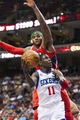 Apr 10, 2013; Philadelphia, PA, USA; Philadelphia 76ers guard Jrue Holiday (11) shoots under pressure from Atlanta Hawks forward Josh Smith (5) during the third quarter at the Wells Fargo Center. The Hawks defeated the Sixers 124-101. Mandatory Credit: Howard Smith-USA TODAY Sports
