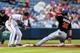 Jul 3, 2013; Atlanta, GA, USA; Miami Marlins center fielder Justin Ruggiano (20) steals third safely before Atlanta Braves third baseman Chris Johnson (23) can make the tag in the first inning at Turner Field. Mandatory Credit: Daniel Shirey-USA TODAY Sports