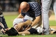 Jul 24, 2013; New York, NY, USA;  Atlanta Braves starting pitcher Tim Hudson (15) is checked on by a trainer after being injured in a collision at first base with New York Mets left fielder Eric Young Jr. (not pictured) during the eighth inning at Citi Field. Mandatory Credit: Anthony Gruppuso-USA TODAY Sports