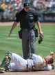Aug 21, 2013; Oakland, CA, USA; Oakland Athletics catcher Stephen Vogt (21) shows the ball to home plate umpire Chad Fairchild (75) after colliding with Seattle Mariners second baseman Dustin Ackley (13, not pictured) during the sixth inning at O.Co Coliseum. Mandatory Credit: Ed Szczepanski-USA TODAY Sports