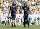 Aug 31, 2013; Morgantown, WV, USA; West Virginia Mountaineers quarterback Paul Millard (14) and running back Charles Sims (3) celebrate after defeating the William & Mary Tribe at Milan Puskar Stadium. The West Virginia Mountaineers won 24-17. Mandatory Credit: Charles LeClaire-USA TODAY Sports