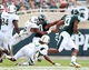 Sep 7, 2013; East Lansing, MI, USA; Michigan State Spartans running back Nick Hill (20) loses the ball while being tackled by South Florida Bulls defensive lineman Anthony Hill (96) during the 2nd half at Spartan Stadium. MSU won 21-6. Mandatory Credit: Mike Carter-USA TODAY Sports