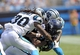 Sep 8, 2013; Charlotte, NC, USA; Seattle Seahawks running back Marshawn Lynch (24) moves the ball as he is tackled by Carolina Panthers safety Charles Godfrey (30) and cornerback D.J. Moore (20) during the game at Bank of America Stadium. Seattle wins 12-7. Mandatory Credit: Sam Sharpe-USA TODAY Sports