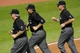 Sep 9, 2013; Cleveland, OH, USA; MLB umpires Dana DeMuth (left), Doug Eddings (center) and Paul Nauert run to the video replay room in the seventh inning during a game between the Cleveland Indians and the Kansas City Royals at Progressive Field. Mandatory Credit: David Richard-USA TODAY Sports