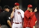 Sep 10, 2013; Cincinnati, OH, USA; Cincinnati Reds pitching coach Bryan Price (right) signals for a relief pitcher during the second after starting pitcher Tony Cingrani (52) leaves the game injured against the Chicago Cubs at Great American Ball Park. Mandatory Credit: Frank Victores-USA TODAY Sports