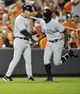 Sep 10, 2013; Baltimore, MD, USA; New York Yankees left fielder Alfonso Soriano (12) is congratulated by third base coach Rob Thomson (59) after hitting a solo home run in the sixth inning against the Baltimore Orioles at Oriole Park at Camden Yards. The Yankees won 7-5. Mandatory Credit: Joy R. Absalon-USA TODAY Sports