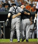 Sep 10, 2013; Baltimore, MD, USA; New York Yankees catcher Austin Romine (53) is helped off the field by head athletic trainer Steve Donohue after taking a foul ball off his helmet in the eighth inning against the Baltimore Orioles at Oriole Park at Camden Yards. The Yankees defeated the Orioles 7-5. Mandatory Credit: Joy R. Absalon-USA TODAY Sports