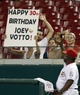 Sep 10, 2013; Cincinnati, OH, USA; Cincinnati Reds first base coach Billy Hatcher (22) throws a ball to a fan holding up a sign for Joey Votto (not pictured) birthday during the eighth inning against the Chicago Cubs at Great American Ball Park. The Cubs defeated the Reds 9-1. Mandatory Credit: Frank Victores-USA TODAY Sports