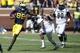 Sep 14, 2013; Ann Arbor, MI, USA; Michigan Wolverines quarterback Devin Gardner (98) runs the ball past Akron Zips safety Anthony Holmes (7) in the fourth quarter at Michigan Stadium. Michigan won 28-24. Mandatory Credit: Rick Osentoski-USA TODAY Sports