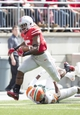 Sep 21, 2013; Columbus, OH, USA; Ohio State Buckeyes running back Ezekiel Elliott (15) breaks through a tackle attempted by Florida A&M Rattlers defensive back Jonathan Pillow (19) at Ohio Stadium. Ohio State won the game 76-0. Mandatory Credit: Greg Bartram-USA TODAY Sports