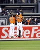 Sep 28, 2013; Baltimore, MD, USA; Baltimore Orioles outfielders Nate McLouth (left) Nick Markakis (right) and Adam Jones (rear) celebrate after a game against the Boston Red Sox at Oriole Park at Camden Yards. The Orioles defeated the Red Sox 6-5. Mandatory Credit: Joy R. Absalon-USA TODAY Sports