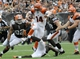 Sep 29, 2013; Cleveland, OH, USA; Cincinnati Bengals quarterback Andy Dalton (14) tries to elude Cleveland Browns defense during the third quarter at FirstEnergy Stadium. The Browns beat the Bengals 17-6. Mandatory Credit: Ken Blaze-USA TODAY Sports