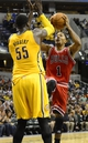 Oct 5, 2013; Indianapolis, IN, USA; Chicago Bulls point guard Derrick Rose (1) puts up a shot against Indiana Pacers center Roy Hibbert (55) at Bankers Life Fieldhouse. Bulls beat Pacers 82-76. Mandatory Credit: Marc Lebryk-USA TODAY Sports