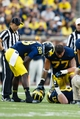 Oct 5, 2013; Ann Arbor, MI, USA; Michigan Wolverines quarterback Devin Gardner (98) and offensive linesman Taylor Lewan (77) check on an injured offensive linesman Patrick Kugler (57) against the Minnesota Golden Gophers at Michigan Stadium. Mandatory Credit: Rick Osentoski-USA TODAY Sports