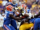 Oct 12, 2013; Baton Rouge, LA, USA; LSU Tigers running back Jeremy Hill (33) hangs onto the football late in the fourth quarter as he is tackled by four Florida Gators at Tiger Stadium. Mandatory Credit: Chuck Cook-USA TODAY Sports