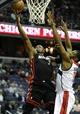 Oct 15, 2013; Washington, DC, USA; Miami Heat guard Dwyane Wade (3) shoots a layup over Washington Wizards power forward Kevin Seraphin (13) during the second half at the Verizon Center. Mandatory Credit: Brad Mills-USA TODAY Sports
