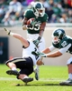 Oct 19, 2013; East Lansing, MI, USA; Michigan State Spartans running back Jeremy Langford (33) is tripped up by Purdue Boilermakers linebacker Sean Robinson (10) during the 2nd half at Spartan Stadium. MSU won 14-0. Mandatory Credit: Mike Carter-USA TODAY Sports