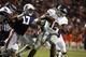Oct 26, 2013; Auburn, AL, USA; Florida Atlantic Owls quarterback Jaquez Johnson (12) avoids Auburn Tigers linebacker Kris Frost (17) during the second half at Jordan Hare Stadium. Mandatory Credit: John Reed-USA TODAY Sports