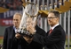 Oct 30, 2013; Boston, MA, USA; Boston Red Sox owner John Henry (right) holds the World Series championship trophy after game six of the MLB baseball World Series against the St. Louis Cardinals at Fenway Park. The Red Sox won 6-1 to win the series four games to two. Mandatory Credit: Robert Deutsch-USA TODAY Sports