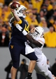Nov 9, 2013; Morgantown, WV, USA; West Virginia Mountaineers quarterback Paul Millard (14) is hit by Texas Longhorns linebacker Steve Edmond (33) at Milan Puskar Stadium. Mandatory Credit: Evan Habeeb-USA TODAY Sports