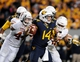 Nov 9, 2013; Morgantown, WV, USA; West Virginia Mountaineers quarterback Paul Millard (14) gets sacked by Texas Longhorns defensive end Jackson Jeffcoat (44) at Milan Puskar Stadium. Mandatory Credit: Evan Habeeb-USA TODAY Sports