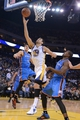 November 14, 2013; Oakland, CA, USA; Golden State Warriors center Andrew Bogut (12, right) shoots the ball Oklahoma City Thunder center Steven Adams (12) during the third quarter at Oracle Arena. The Warriors defeated the Thunder 116-115. Mandatory Credit: Kyle Terada-USA TODAY Sports