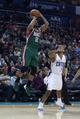 Nov 29, 2013; Charlotte, NC, USA; Milwaukee Bucks shooting guard Gary Neal (12) shoots the ball while Charlotte Bobcats point guard Ramon Sessions (7) defends during the first half at Time Warner Cable Arena. Mandatory Credit: Jeremy Brevard-USA TODAY Sports