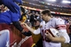 Dec 1, 2013; Landover, MD, USA;  New York Giants quarterback Eli Manning (10) hands a wrist band to a fan in the stands after the Giants' game against the Washington Redskins at FedEx Field. The Giants won 24-17. Mandatory Credit: Geoff Burke-USA TODAY Sports