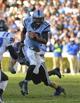 Nov 30, 2013; Chapel Hill, NC, USA; North Carolina Tar Heels quarterback Marquise Williams (12) runs as Duke Blue Devils linebacker Kelby Brown (59) defends in the fourth quarter. The Blue Devils defeated the Tar Heels 27-25 at Kenan Memorial Stadium. Mandatory Credit: Bob Donnan-USA TODAY Sports