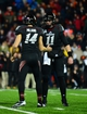 Dec 5, 2013; Cincinnati, OH, USA; Cincinnati Bearcats kicker Tony Miliano (14) is congratulated by quarterback Brendon Kay (11) after kicking a field goal to send to game into overtime during the fourth quarter against the Louisville Cardinals at Nippert Stadium. Mandatory Credit: Andrew Weber-USA TODAY Sports