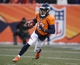 Dec 8, 2013; Denver, CO, USA; Denver Broncos kick returner Andre Caldwell (12) returns a kick during the second half against the Tennessee Titans at Sports Authority Field at Mile High. The Broncos won 51-28.  Mandatory Credit: Chris Humphreys-USA TODAY Sports