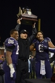 Dec 27, 2013; San Francisco, CA, USA; Washington Huskies interim coach Marques Tuiasosopo (center), tailback Bishop Sankey (25) and defensive end Hau'oli Kikaha (8) hold the championship trophy after the 2013 Fight Hunger Bowl against the BYU Cougars at AT&T Park. Washington defeated BYU 31-16. Mandatory Credit: Kirby Lee-USA TODAY Sports