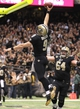 Dec 29, 2013; New Orleans, LA, USA; New Orleans Saints quarterback Drew Brees (9) goes up to dunk the ball in celebration after scoring a touchdown against the Tampa Bay Buccaneers as teammate Zach Strief (64) runs to congratulate him in the second half at the Mercedes-Benz Superdome. New Orleans defeated Tampa Bay 42-17. Mandatory Credit: Crystal LoGiudice-USA TODAY Sports