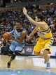 Jan 3, 2014; Denver, CO, USA; Memphis Grizzlies point guard Mike Conley (11) drives to the net against Denver Nuggets shooting guard Evan Fournier (94) in the second quarter at the Pepsi Center. Mandatory Credit: Isaiah J. Downing-USA TODAY Sports