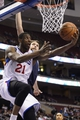 Jan 15, 2014; Philadelphia, PA, USA; Philadelphia 76ers forward Thaddeus Young (21) shoots under pressure from Charlotte Bobcats forward Josh McRoberts (11) during the fourth quarter at the Wells Fargo Center. The Sixers defeated the Bobcats 95-92. Mandatory Credit: Howard Smith-USA TODAY Sports