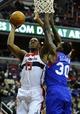 Jan 20, 2014; Washington, DC, USA; Washington Wizards center Kevin Seraphin (13) shoots as Philadelphia 76ers center Dewayne Dedmon (30) defends during the first half at Verizon Center. Mandatory Credit: Brad Mills-USA TODAY Sports