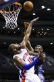 Feb 18, 2014; Auburn Hills, MI, USA; Charlotte Bobcats center Bismack Biyombo (0) shoots on Detroit Pistons power forward Greg Monroe (10) in the first half at The Palace of Auburn Hills. Mandatory Credit: Rick Osentoski-USA TODAY Sports