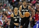 February 18, 2014; Los Angeles, CA, USA; San Antonio Spurs point guard Patty Mills (8) moves the ball up court as power forward Tim Duncan (21) trails against the Los Angeles Clippers during the second half at Staples Center. Mandatory Credit: Gary A. Vasquez-USA TODAY Sports